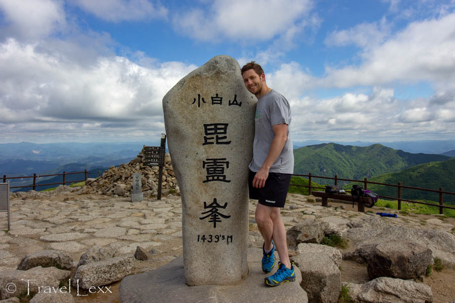A man posing with a marker at the top of Birobong Peak in Sobaeksan National Park