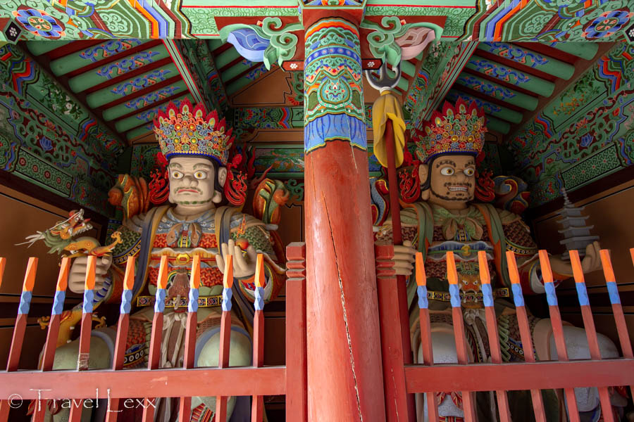 Two colourful figures and a pillar guard a gate to Beomeosa Temple