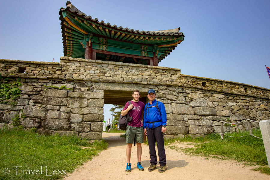 Two men standing in front of a 17th century fortress gate on Geumjeongsan Mountain