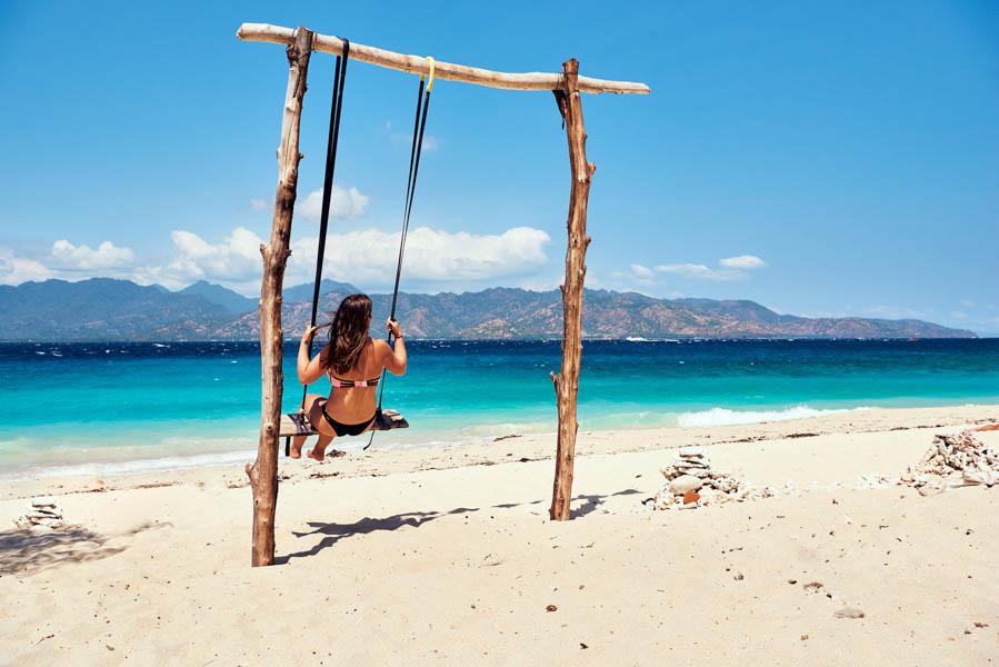 A woman using a swing at a white sand beach