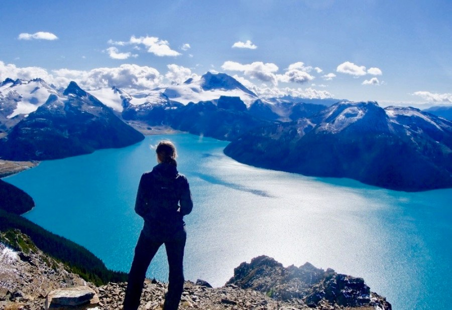 A woman standing at the top of Panorama Ridge hiking trail looking out over Garibaldi Lake