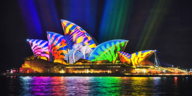 Colourful image projected on the side of the Sydney Opera house during an economical vacation in Sydney.