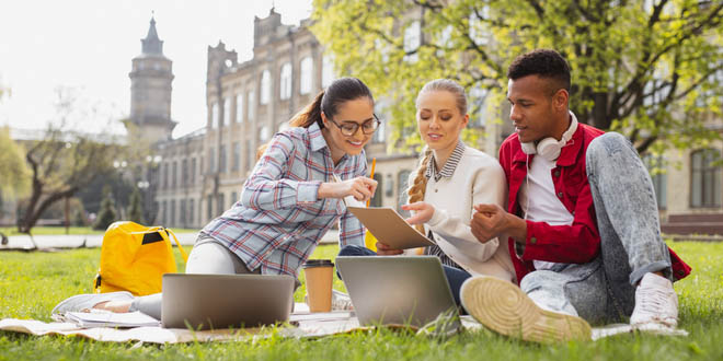 University students sitting outside in a campus park while studying abroad.