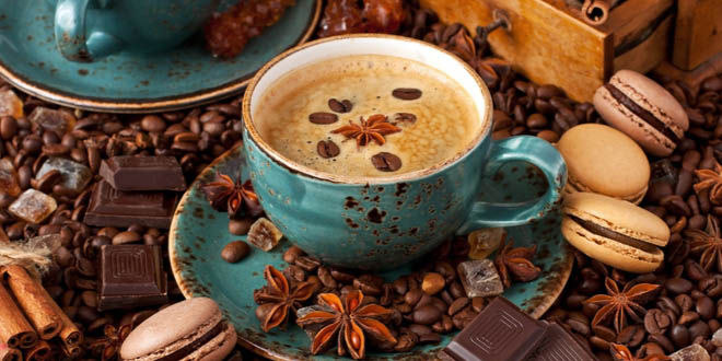 Coffe cup over coffee beans, spices, chocolate and other coffee foods.