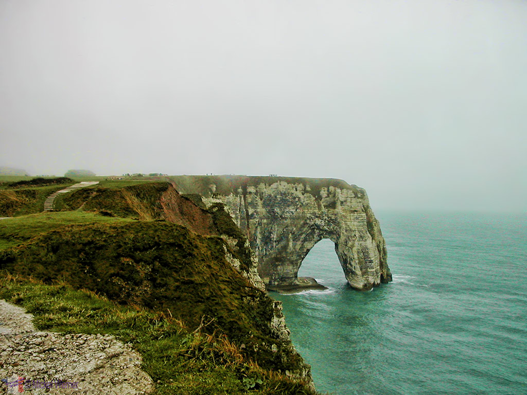 Hiking path to the top of the Aval cliffs of Etretat with a view of the Manneporte cliff and arche