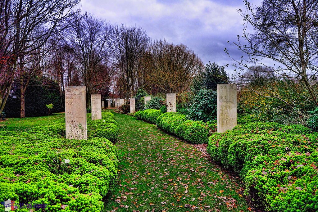 Path with named pillars at the reporters memorial in Bayeux