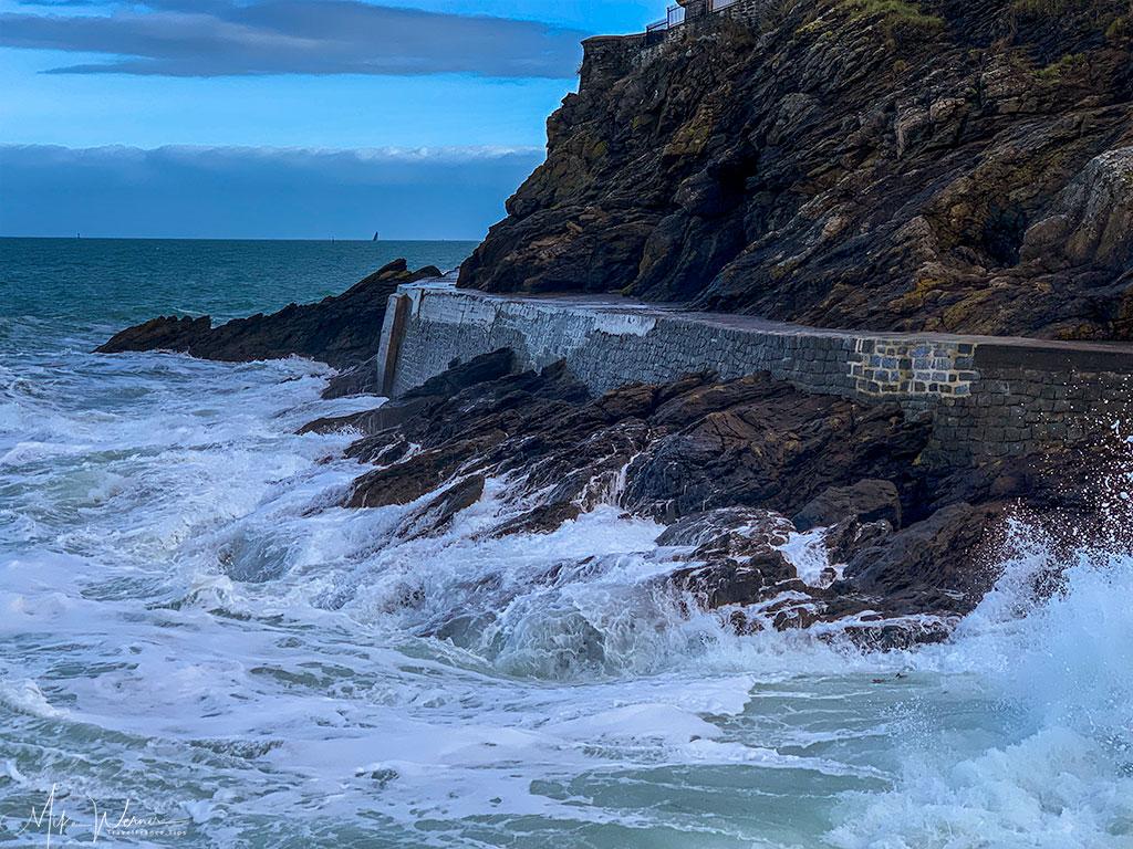 The Dinard promenade with waves crashing onto it'