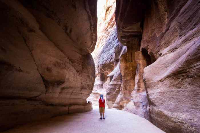 A small boy is enveloped by the walls of the Siq in the City of Petra, Jordan