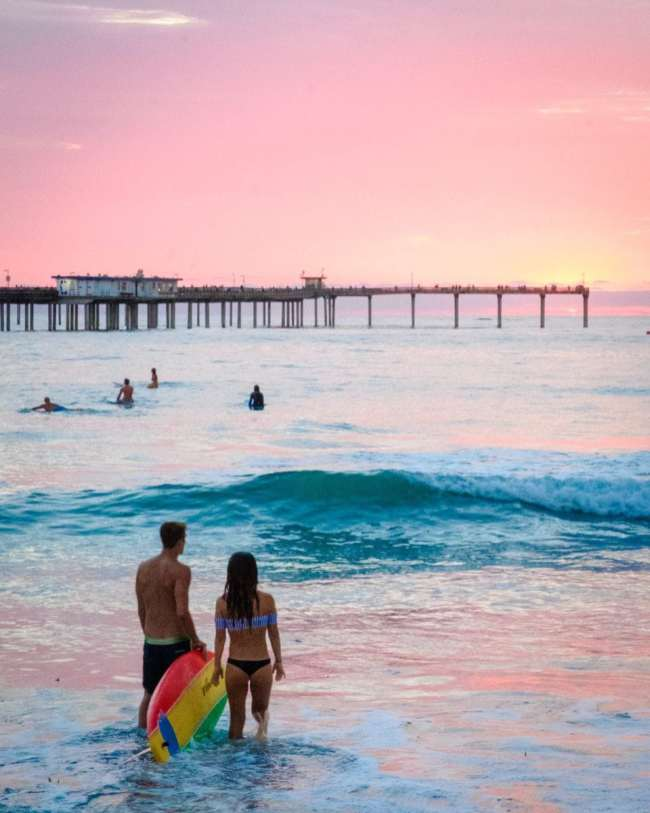 Surfers watch the sunset on Ocean Beach in San Diego along the Pacific Coast Highway