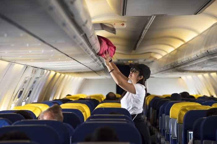 Traveler opens overhead locker on airplane