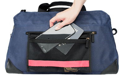 woman demonstrating where the pockets are on the Pakt One Carry-On