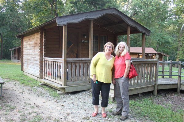 Two hags from DC and Poolesville in front of a rustic cabin
