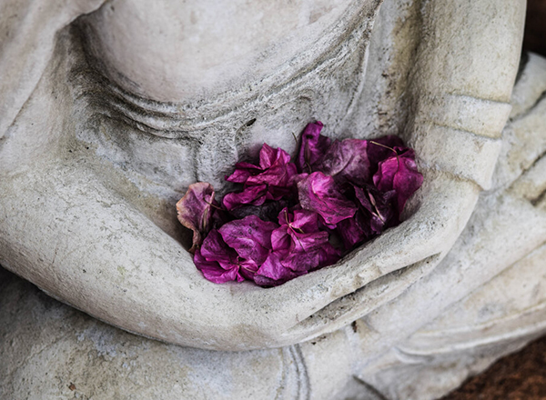 Buddah sculpture with purple flowers
