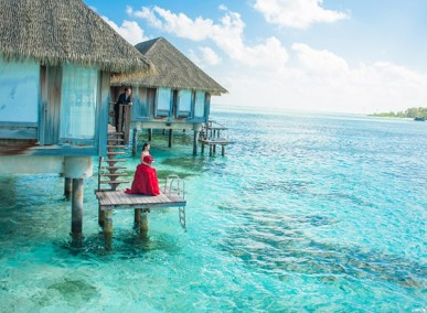 Woman on porch of overwater bungalows