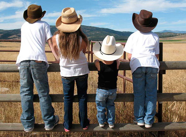 Kids in cowboy hats looking over a fence