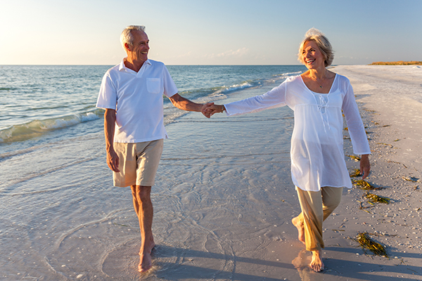 Older couple holding hands on tropical beach