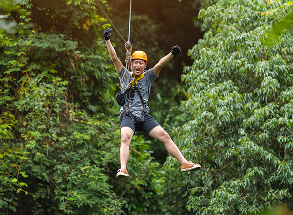 Man ziplining through jungle
