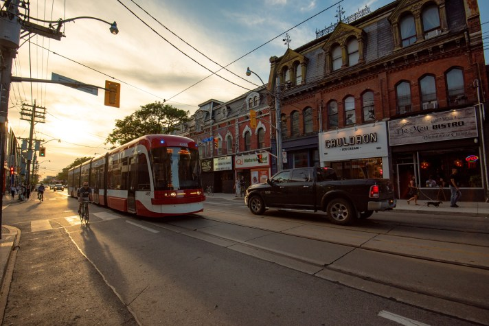 A streetcar travels on Queen Street West at dusk