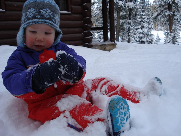 Finn sits in his puffy snowsuit and plays in the snow.