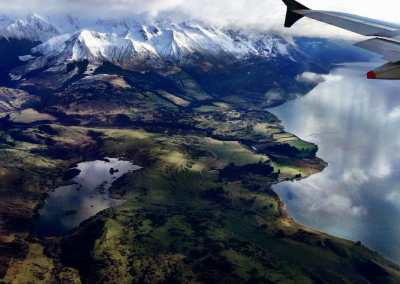 A stunning view of the landscape of a lake, rolling green hills and snow capped mountains as the plane arrives into Queenstown, NZ