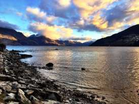 A colorful sunset over the lake and mountains of Queenstown, NZ