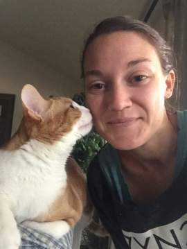 Tayler receiving a kiss on the cheek from a cat