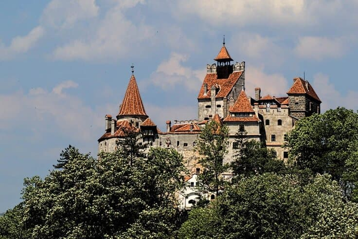 The top of Bran Castle seen through the thick forest in Transylvania.