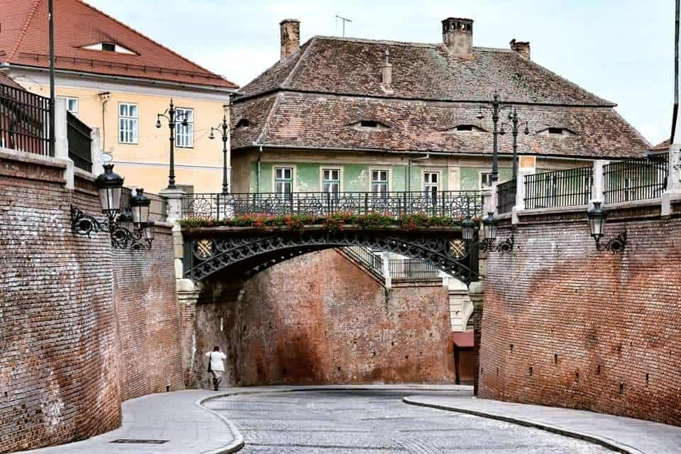 Bridge of Lies in Sibiu with red flowers along the bridge and a lone woman walking underneath.