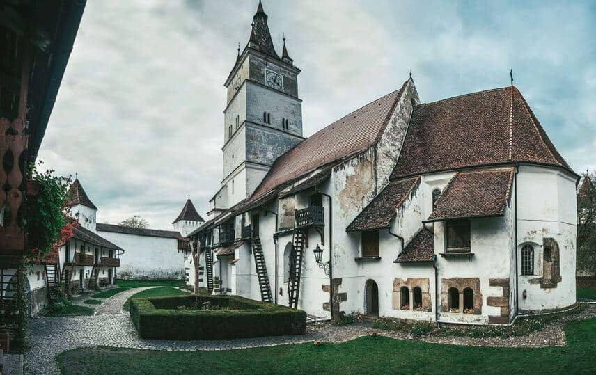 One of Tranylvania's many fortified churches, under cloudy sky with manicured hedges on the front lawn.