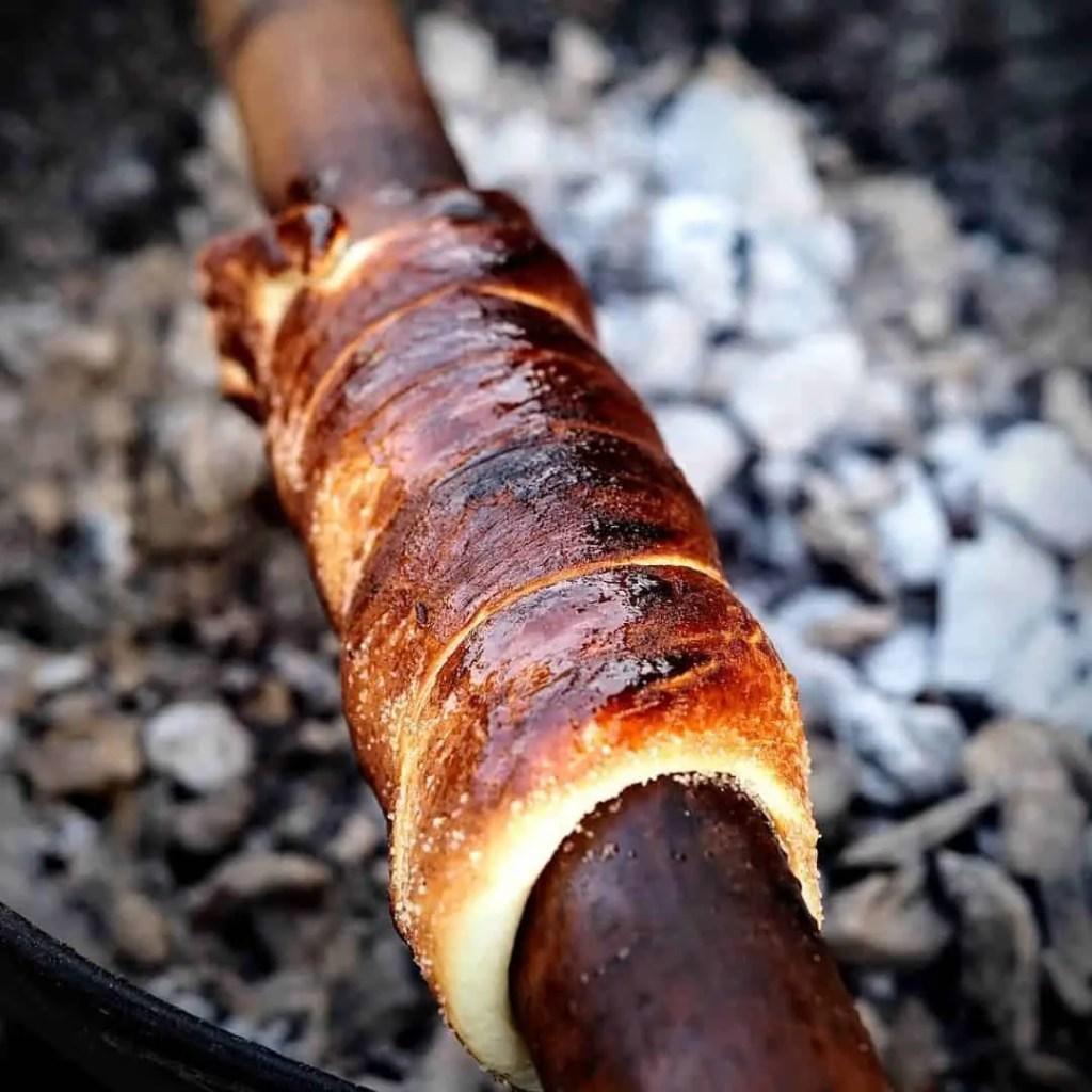 Kurtoskalacs aka chimney cake roasting on a spit, a traditional Hungarian/Romanian dessert local to Transylvania.