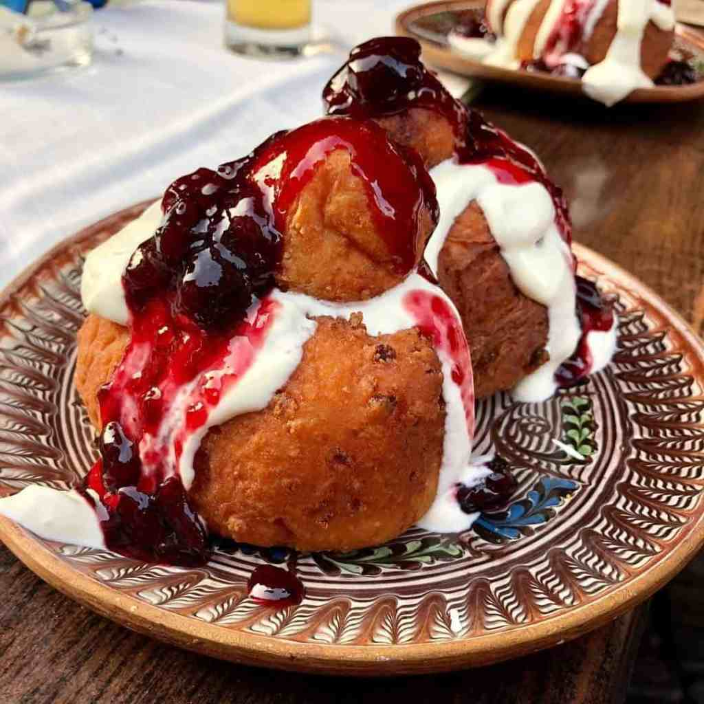 Large round donuts (papanasi) covered in red fruit and sour cream sauce on traditional painted Romanian plate.