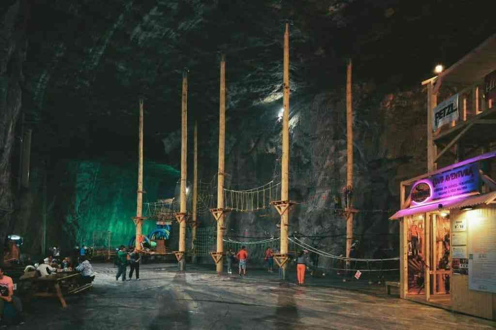 Interior of Praid salt mine with green and purple neon lights and large poles reaching the ceiling.