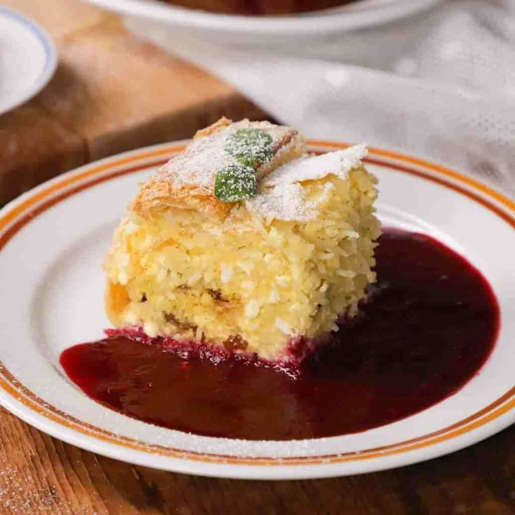 Vargabeles, a sort of noodle pie that is a traditional Transylvanian dessert (Hungarian/Romanian) on a plate with a berry sauce and powdered sugar.
