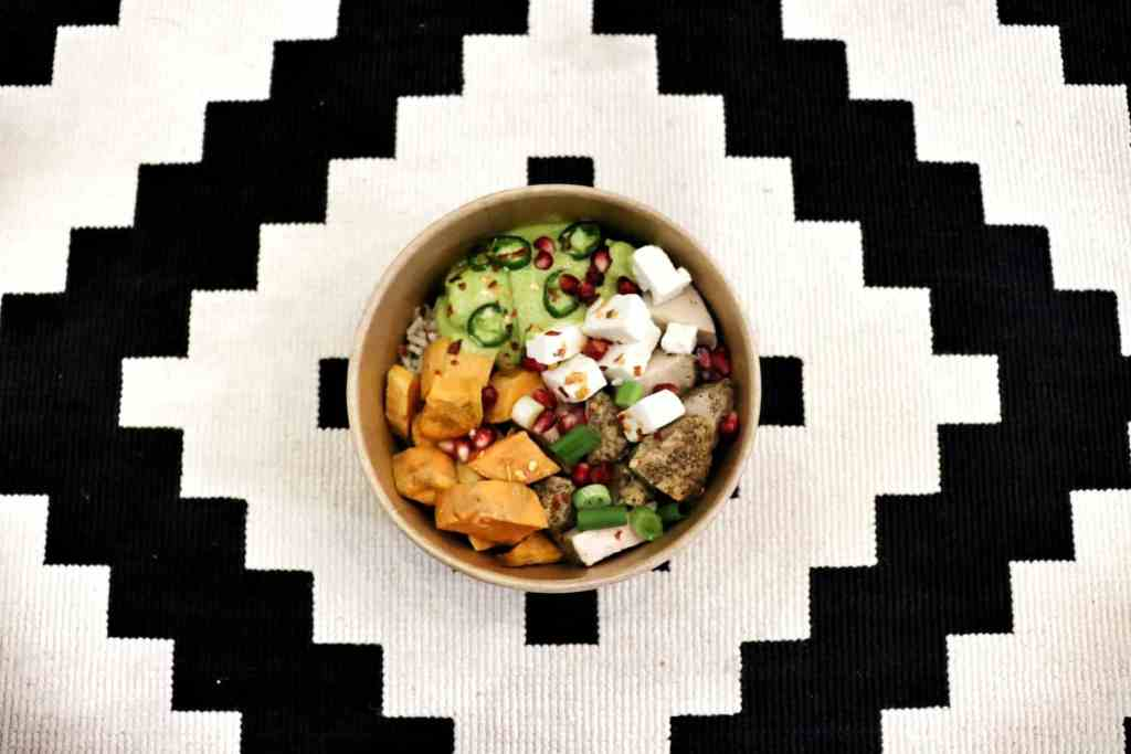 Vegetarian bowl of veggies, tofu, and jalapenos on a black and white table cloth.