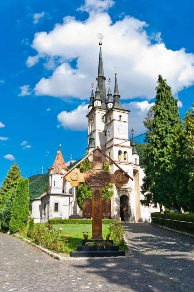 St. Nicholas' Church in Transylvania, Brasov, Romania with green shrubs and blue skies.