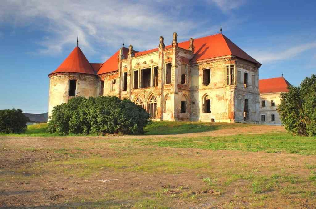 Banffy Castle in Transylvania, Romania with red roofs, green grass, and blue skies.