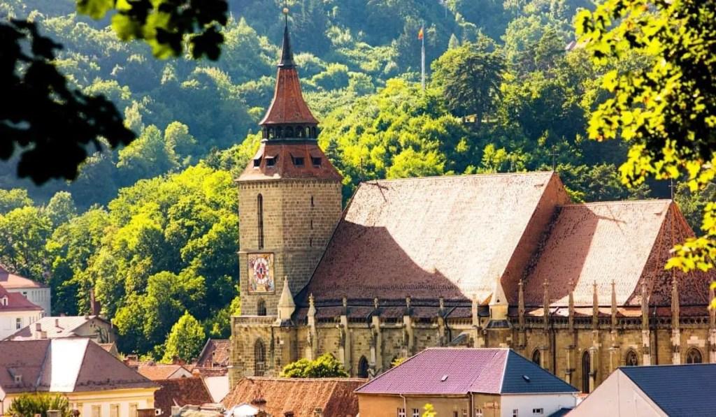 Biserica Neagra, view of the Black Church through green trees in Brasov, Romania.