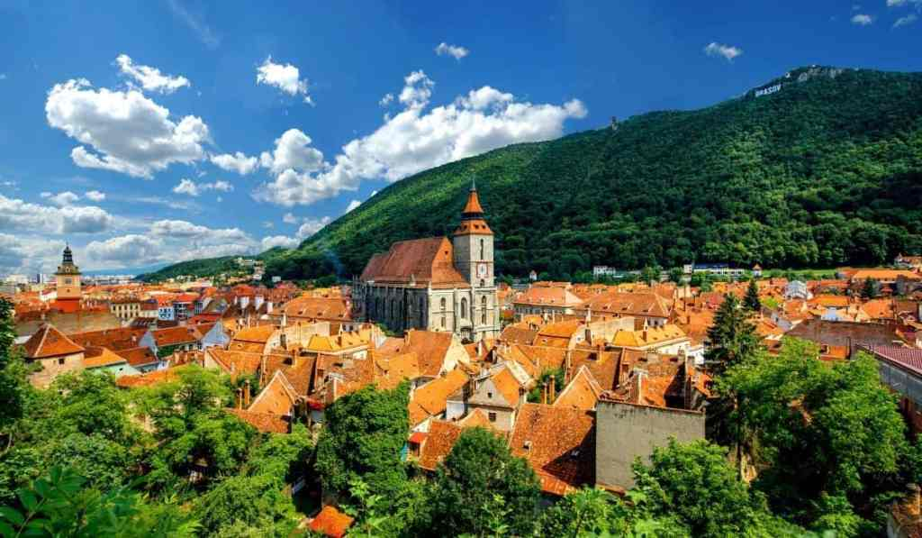 Red rooftops of Brasov in the forest-covered mountains of Transylvania.