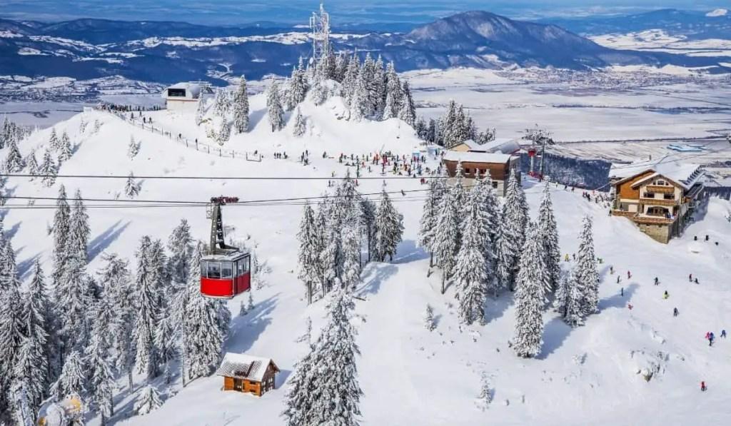 Snow covered slopes with red ski lifts in Poiana, Transylvania, Romania.