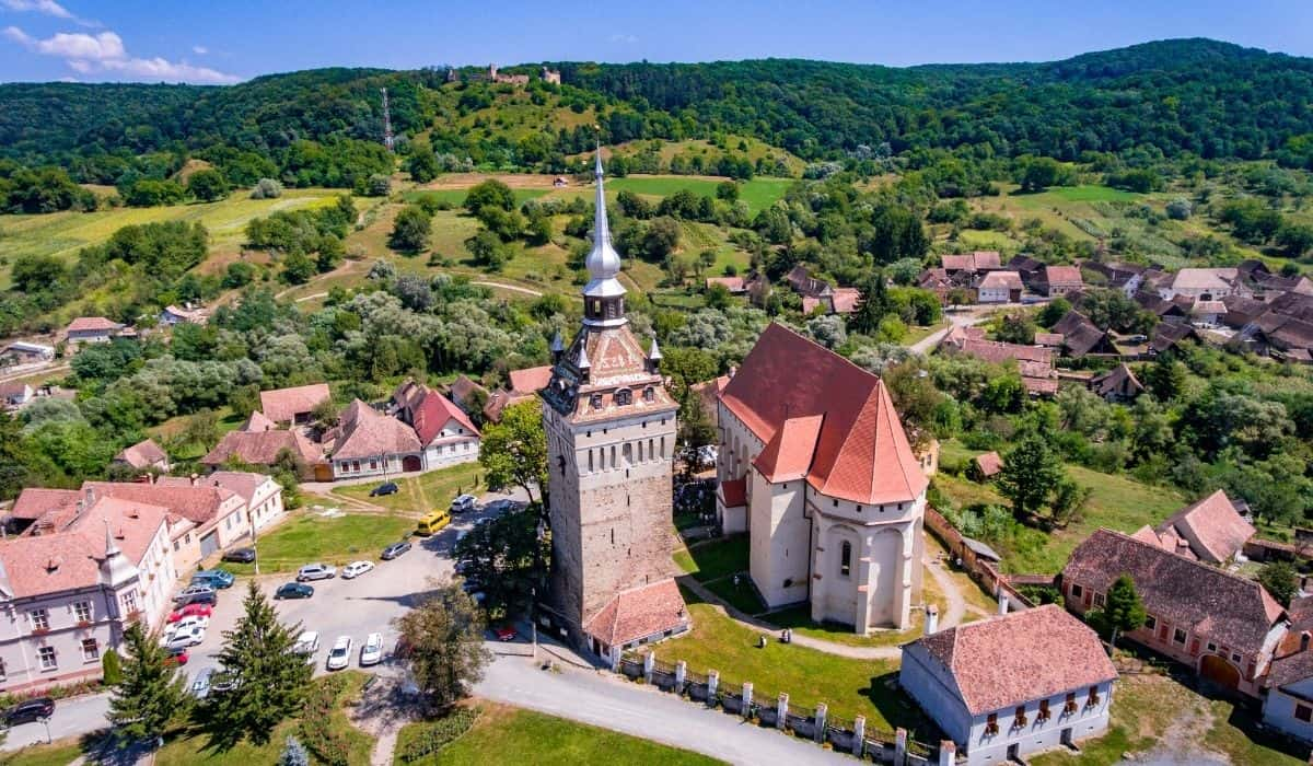 Fortified church of Saschiz from an aerial perspective with green trees and blue skies in the background.