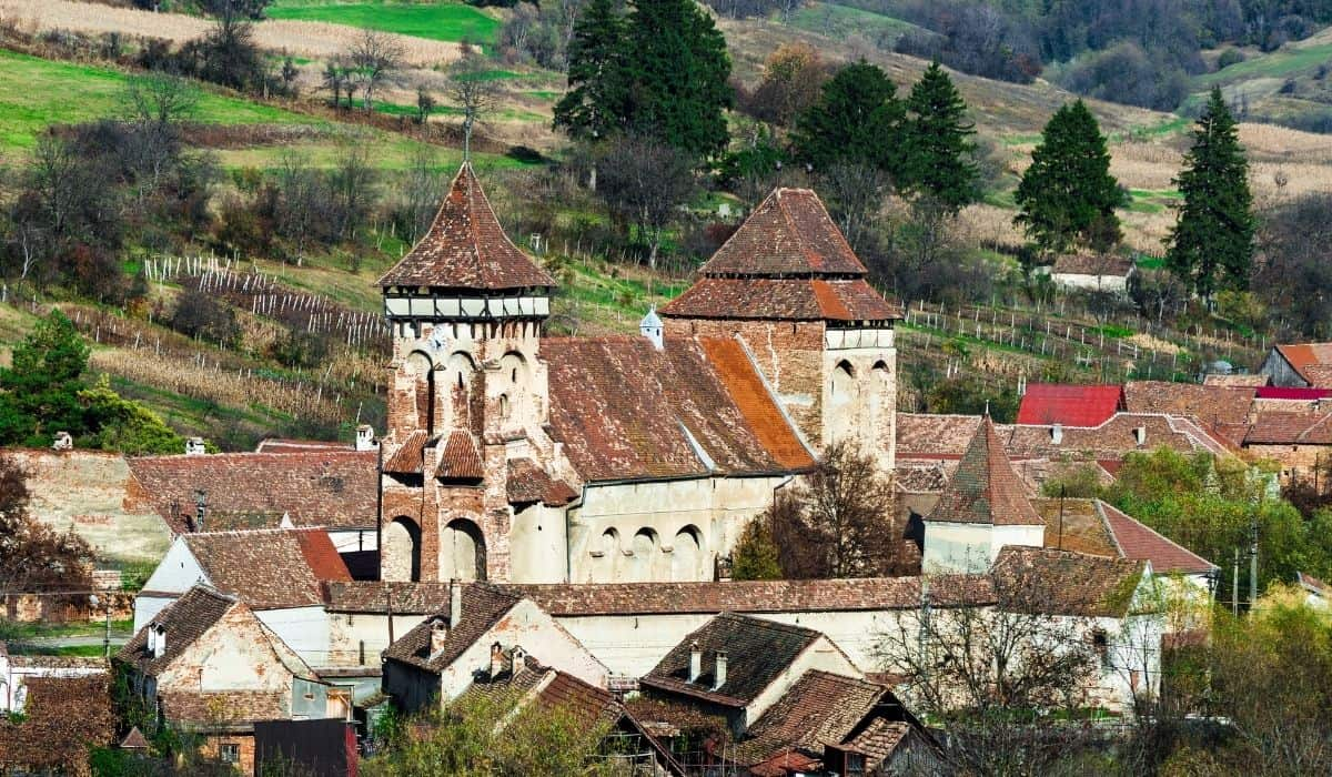 Fortified church of Valea Viilor with rustic farmlands in the background.