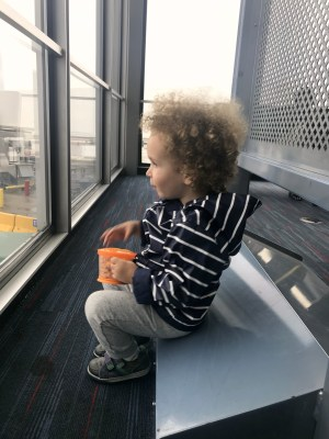Toddler watching airplanes take off and land