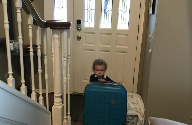 Toddler with suitcase at Airbnb for families