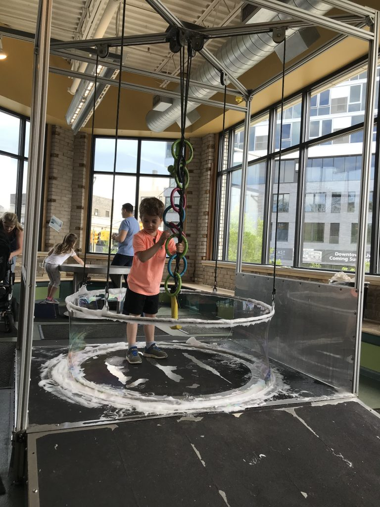 Kindergartner playing with the stand up bubble pulley at the Grand Rapids Children Museum