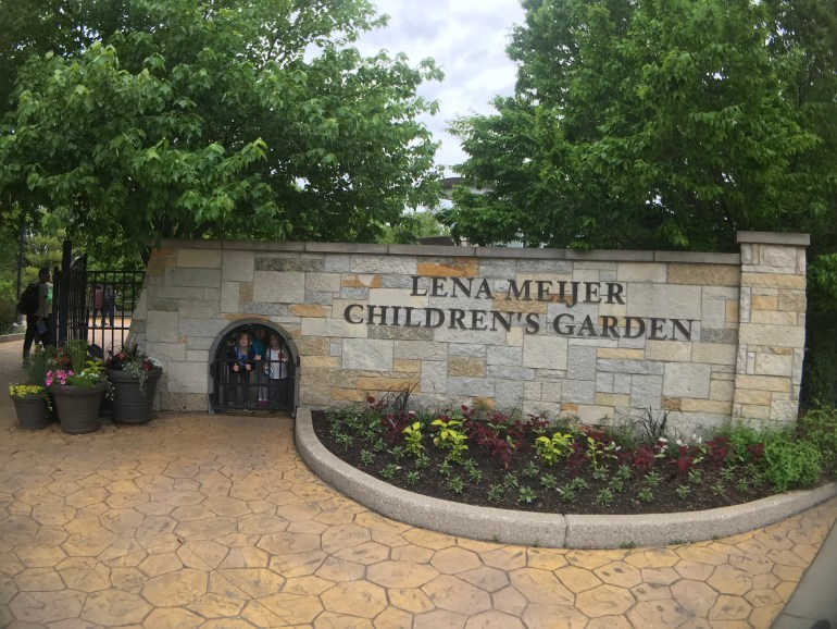 Lena Meijer Children's Garden Entryway with three children looking through a little gate, at the Frederic Meijer Gardens and Sculpture Park