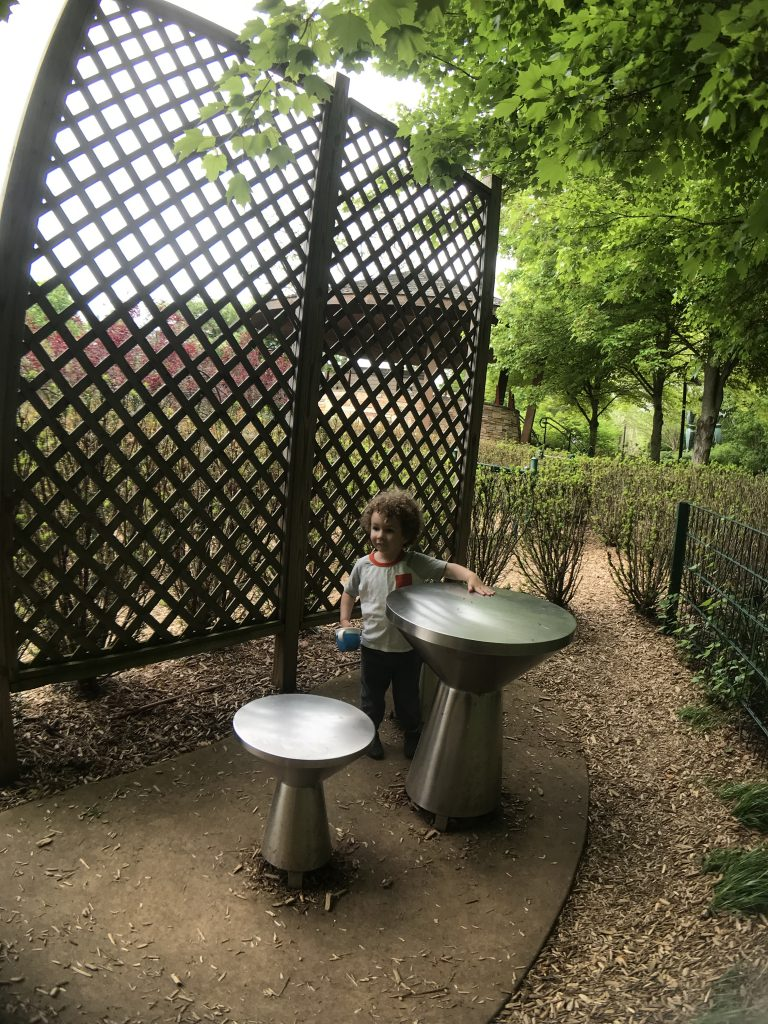 Child playing metal drums at Frederic Meijer Gardens and Sculpture Park