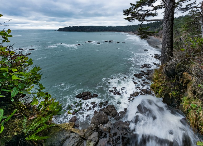 View of the Pacific Coastline waterfall, dramatic cliffs, and the ocean at Third Beach in Olympic National Park