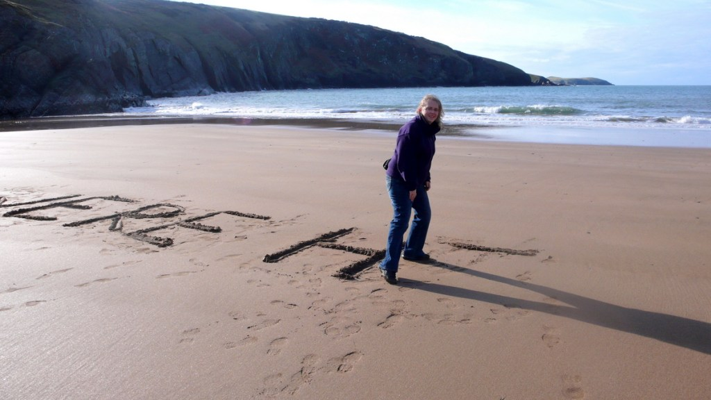 Writing in the sand at Mwnt....from a travel blog by traveljunkiegirl.com