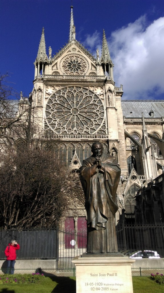 Sculpture in the Square Jean XIII garden with Notre Dame's southern rose window, Paris; from a travel blog by www.traveljunkiegirl.com