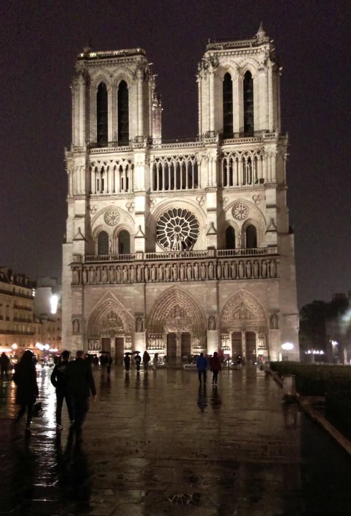 Notre-Dame looks beautiful lit at night, Paris; from a travel blog by www.traveljunkiegirl.com